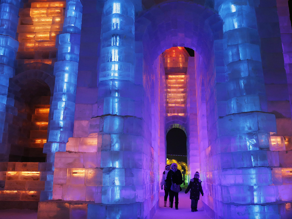 People visit ice sculptures illuminated by coloured lights during a trial operation ahead of the 31st Harbin International Ice and Snow Festival in the northern city of Harbin, Heilongjiang province, January 4, 2015. The winter festival will be officially opened on January 5, 2015.  REUTERS/Kim Kyung-Hoon (CHINA - Tags: ANNIVERSARY SOCIETY)